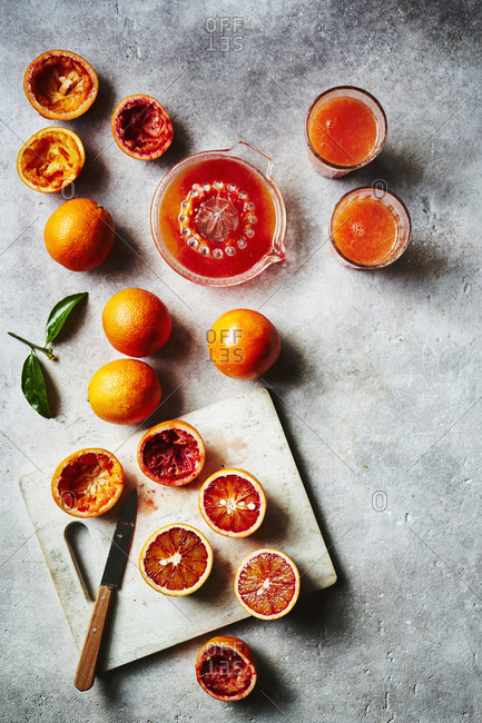 Blood oranges being cut up and squeezed into juice as a prep scene.