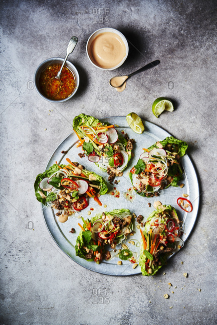 Five Vietnamese lettuce wraps shot from above with a wedge of lime and sauce and sriracha at the top of the image. Ingredients include beef, rice noodles, carrot, cucumber, spring onions, chili, peanuts, coriander, mint and squeeze of lime.