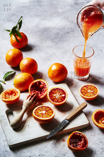 Blood oranges being cut up, squeezed into juice and poured,  as a prep scene.
