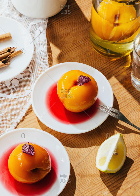Sweet peaches on white plates, lemon, and cinnamon on wood table