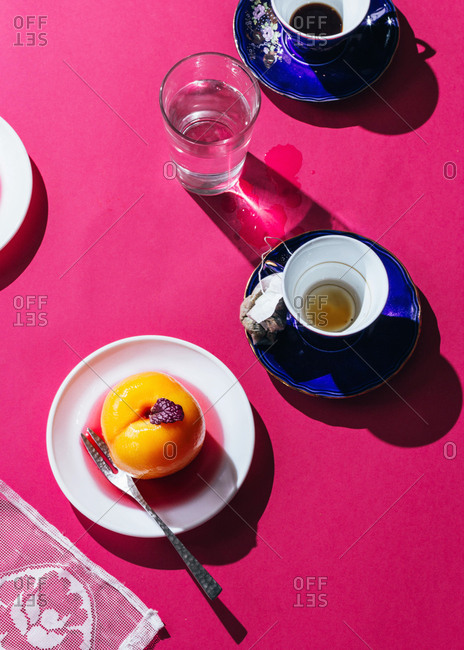 Peach, coffee and tea on a pink table