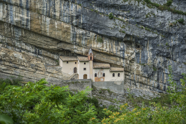 July 5, 2016: Italy, Trentino Alto Adige, Rovereto . Eremo di San Colombano is reached by walking a short path and a staircase of 102 steps, dug directly into the rock. The hermitage is built on an overhang of about 120 meters. Protected from the elements by a natural rock roof it seems to have been inhabited since 753. The date of construction of the church and the hermitage annex dates back to the 10th century