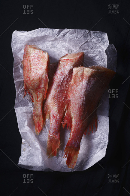 Raw uncooked fish perch on black background. Overhead view