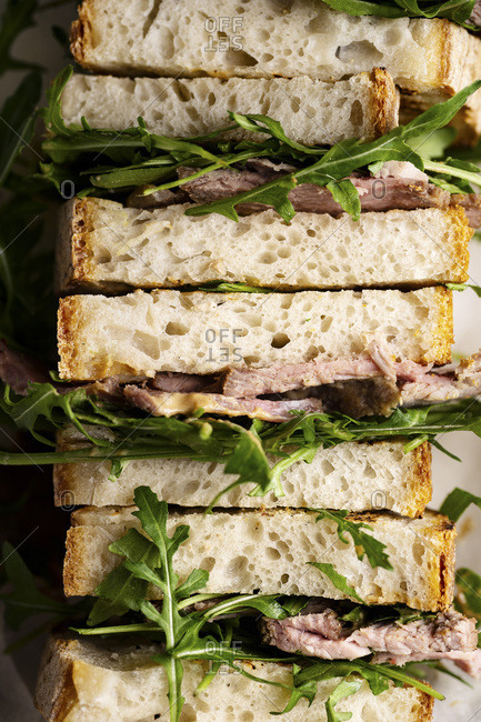 Close up shot of roast beef sandwich with arugula and mustard
