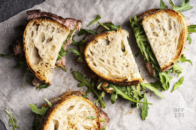 Overhead image of roast beef sandwich with arugula and mustard