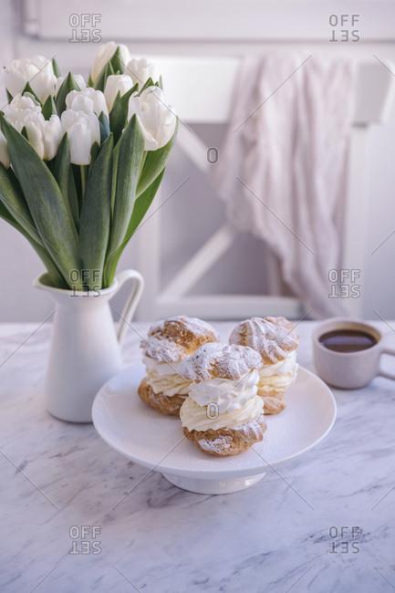 Cream puff desserts on a white cake stand