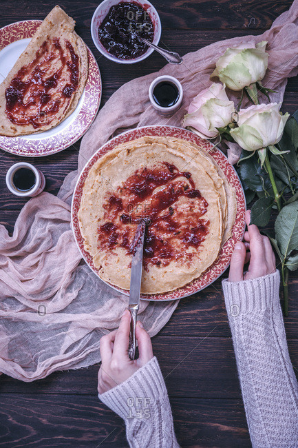 Woman eating crepes with cherry jam and coffee for breakfast