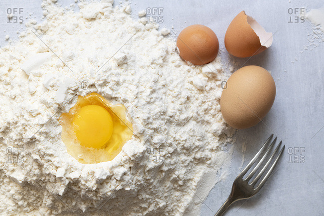 A raw egg in flour with a fork.