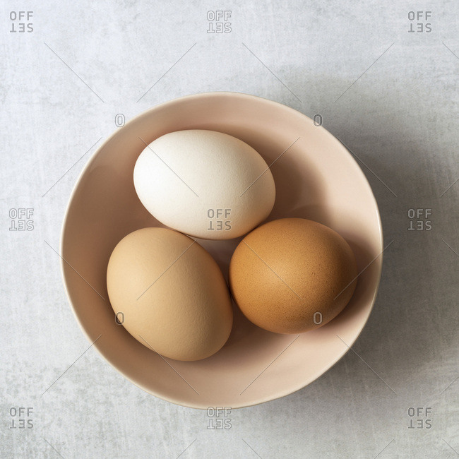 Close-up view of three hen eggs in a bowl.