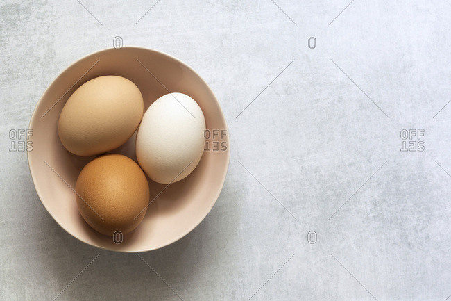 Brown and white hen eggs in a bowl.