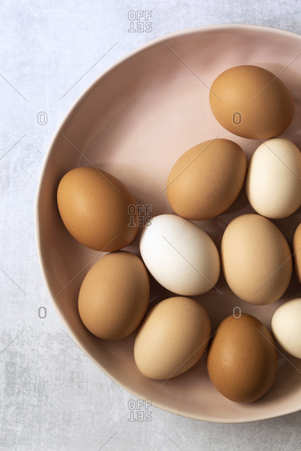 A bowl of brown and white hen eggs.