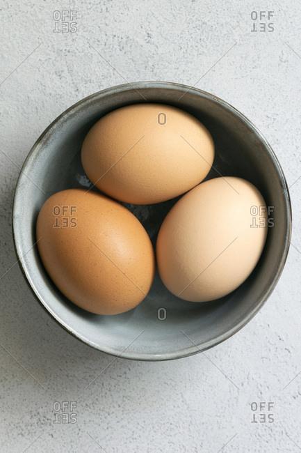 Three hen eggs in a bowl.