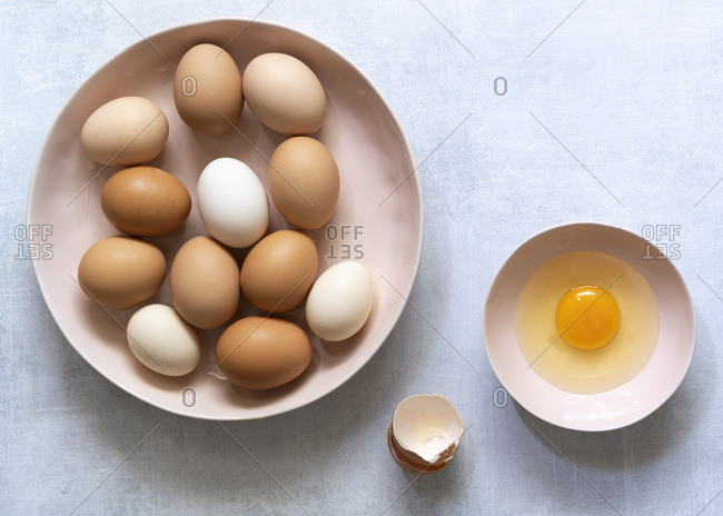 Brown and white hen eggs with a cracked egg in a small bowl.