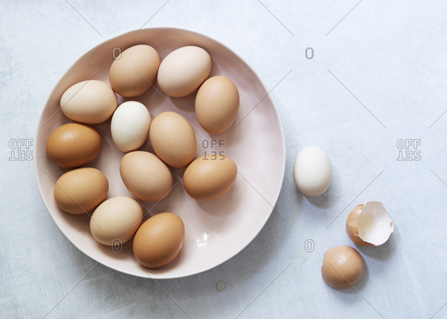 Brown and white eggs in a bowl with egg shells at the side.