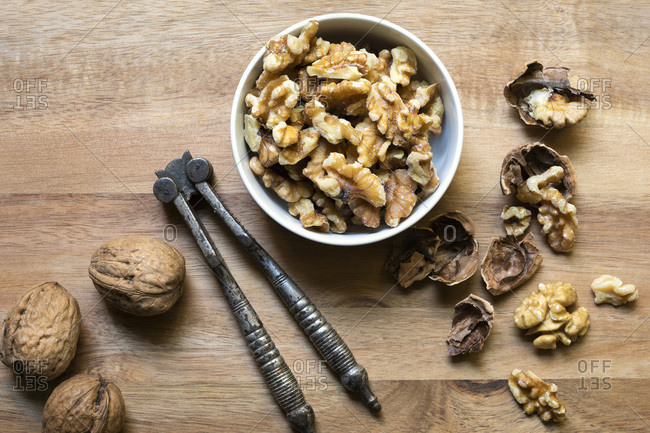 Cracked walnut pieces in a bowl beside whole walnuts and a vintage nut cracker.