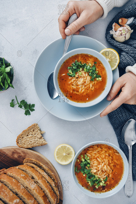 Woman eating Turkish tomato orzo soup garnished with parsley served in light blue bowls on a grey background. Accompanied by bread slices.