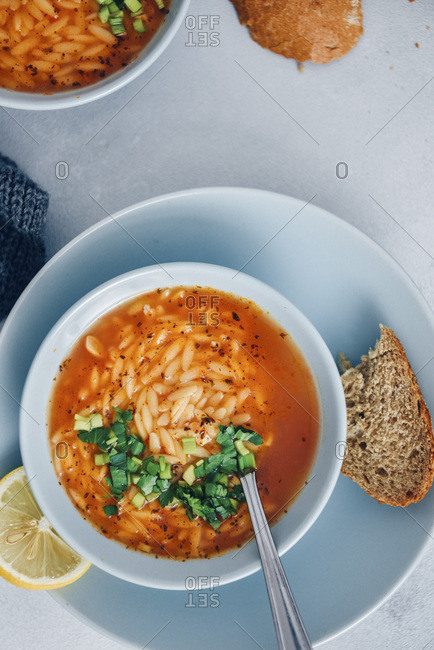 Turkish tomato orzo soup garnished with parsley is served in light blue bowls on a grey background. Accompanied by bread slices.