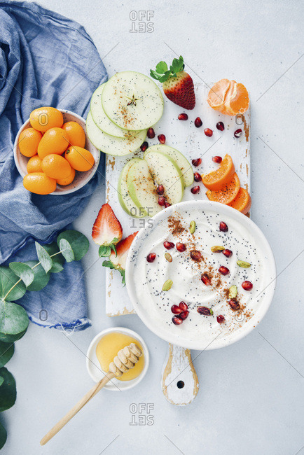 Yogurt fruit dip garnished with poppy seeds, pomegranate arils, pistachios and cinnamon served in a white ceramic bowl on a white wooden board.
