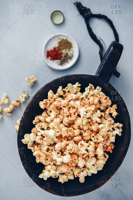 Spicy popcorn served in a large wooden bowl accompanied by spices in a small plate and a bottle cap.