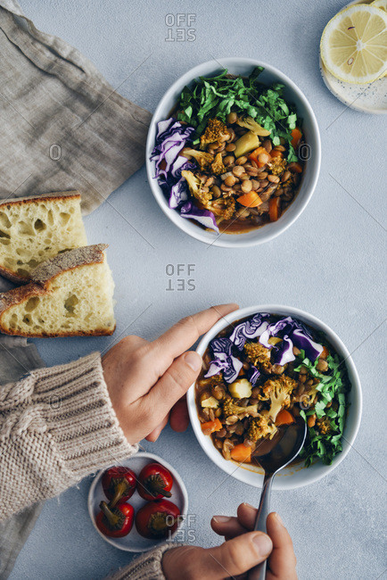 Vegan lentil stew with broccoli and carrot garnished with shredded red cabbage and chopped parsley served in three white bowls. Accompanied by bread slices, pickled chili and lemon slices on a grey background.