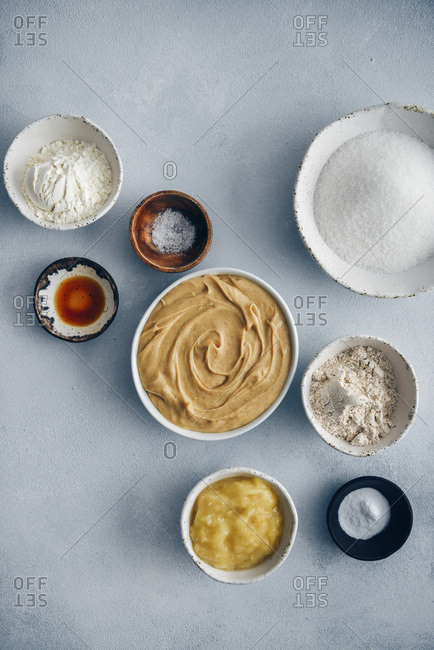 Ingredients for vegan peanut butter cookies are photographed from top view on a grey background.
