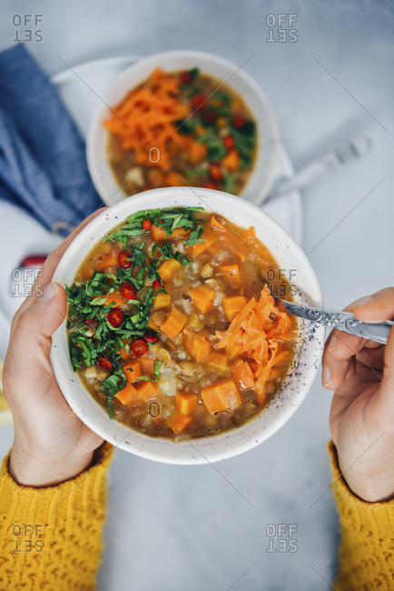 A woman with yellow cardigan holding a bowl of vegan carrot soup with rice, lentils and celeriac, garnished with mint and chili peppers.