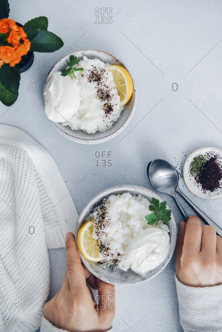 Woman eating savory rice porridge garnished with yogurt, lemon wedges, sumac and dried mint.