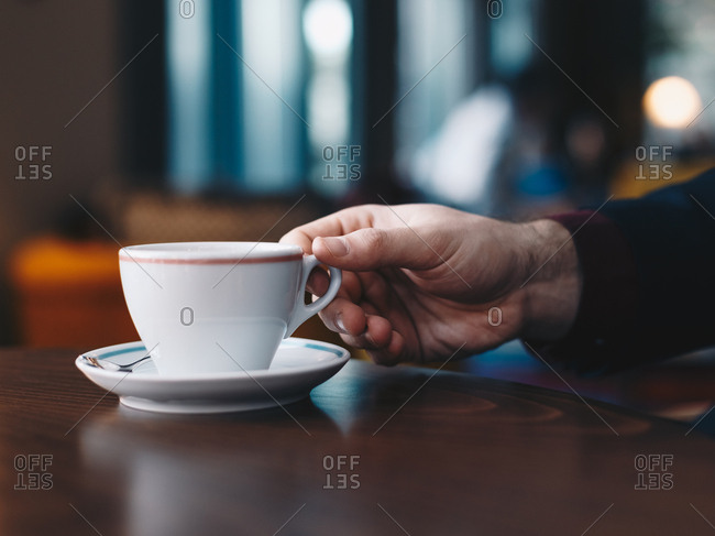 Detail shot of a male hand holding a coffee mug in a restaurant.