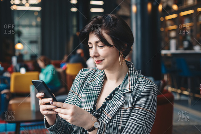 Close up portrait of a successful young woman using a mobile phone, enjoying a downtime during a break from work, sitting in a cafe bar.