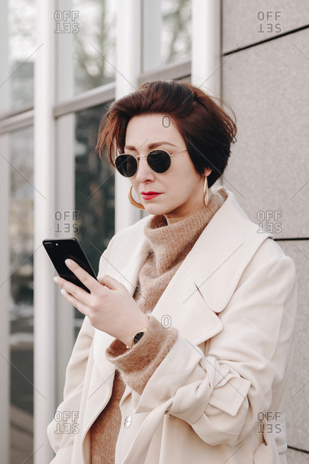 Portrait of a fashionable female freelancer posing in the city, wearing a modern coat and texting on her cellphone.