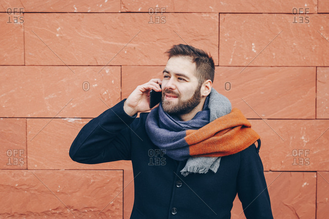 Trend following young man in the middle of a conversation over his cellphone, wearing a fashionable overcoat and a scarf.