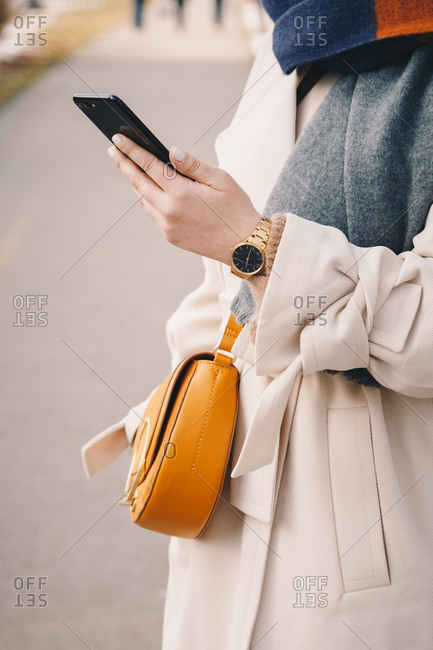 Close up of a chic girl's hand holding a cellphone outside, wearing a white trench coat, a handbag and a wristwatch.