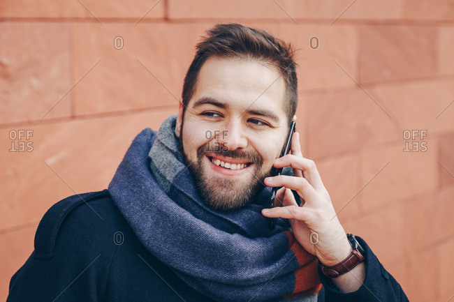Trend following young man talking on his cellphone and being happy with the conversation, wearing an overcoat and a scarf.