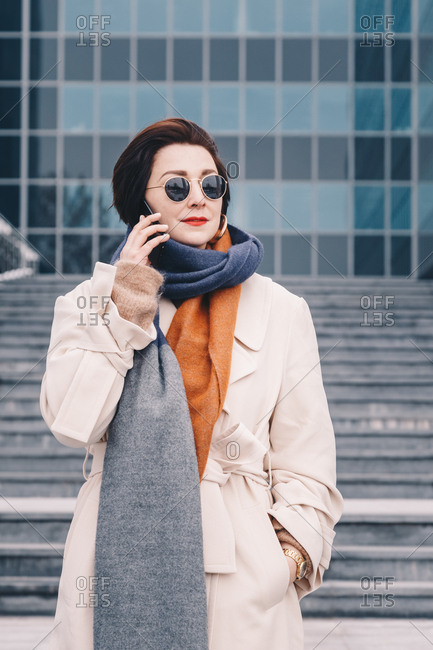 Portrait of a chic young businesswoman posing in front of a modern building, outside of her office, wearing a trench coat and chatting over her cellphone.