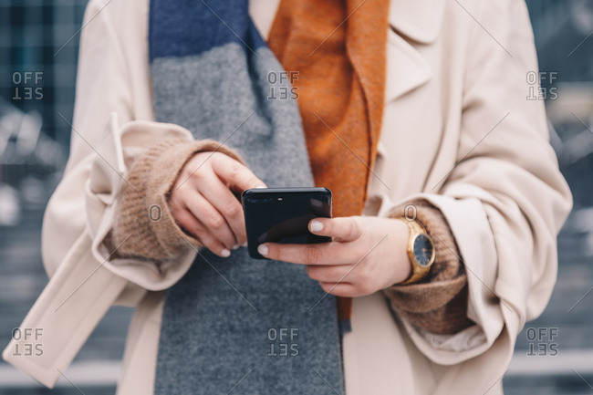 Detail shot of woman's hands holding a mobile phone and wearing an analog hand watch, in urban surroundings.