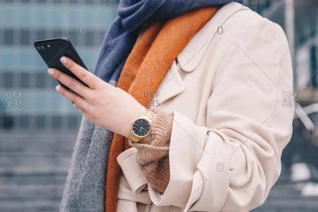 Detail shot of a female hand using a mobile phone and wearing an analog hand watch, in urban surroundings.
