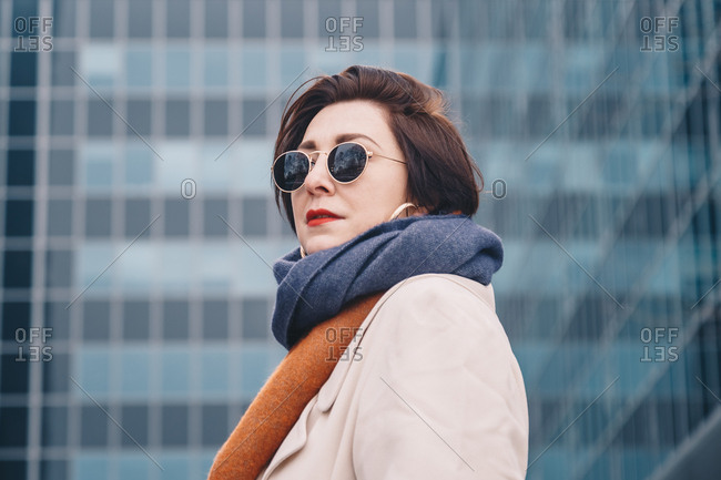 Portrait of a fashionable female freelancer wearing sunglasses and posing in a white trench coat in front of an urban office building.