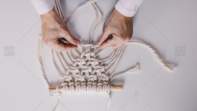 Detail shot of woman's hands weaving macrame in a private workshop.