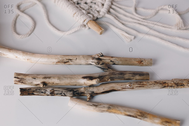 Detail shot of threads and driftwood branches that are used for making macrame.