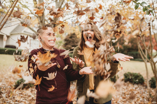 Cute lesbian couple playing with autumn leaves