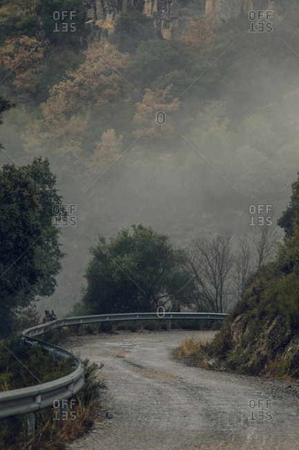 Winding road surrounded by fog in the Pyrenees Mountains, Europe