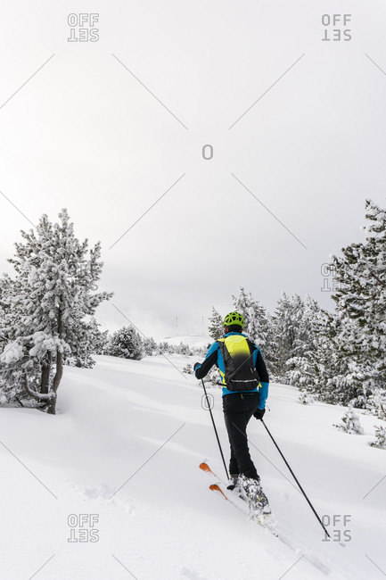 Rear view of man skiing on a snowy hill