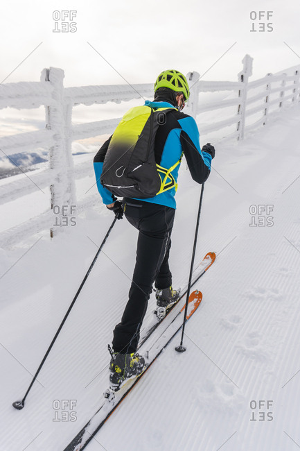 Rear view of man climbing on a snowy hill with skis