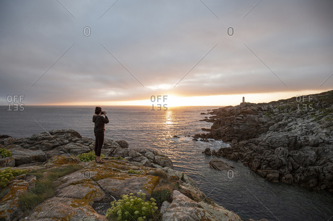 Woman taking pictures of sunset along the coast of Lleida, Spain