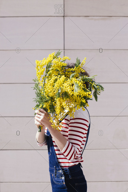 Side view of woman holding bouquet of yellow flowers in front of her face