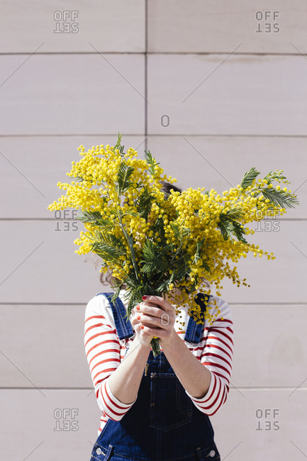 Woman holding bouquet of yellow flowers in front of her face