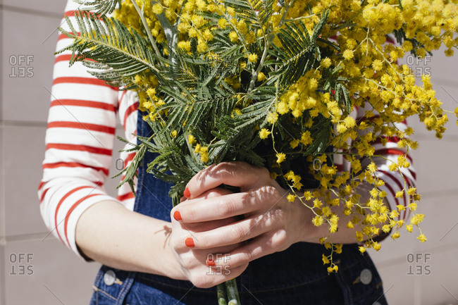 Close up of a woman holding bouquet of yellow flowers