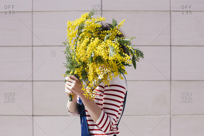 Side view of woman holding yellow flowers in front of her face