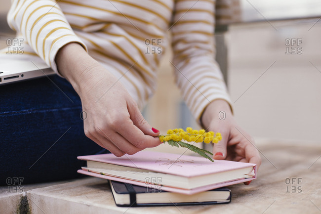 Woman placing yellow flowers on top of a book and thank you note