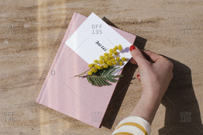 Hand touching yellow flowers on top of a book and thank you note